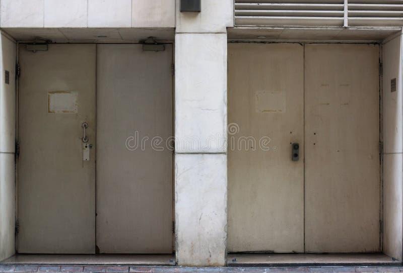 Achterdeur of achterdieingang van een gebouw in wit wordt geschilderd stock afbeeldingen