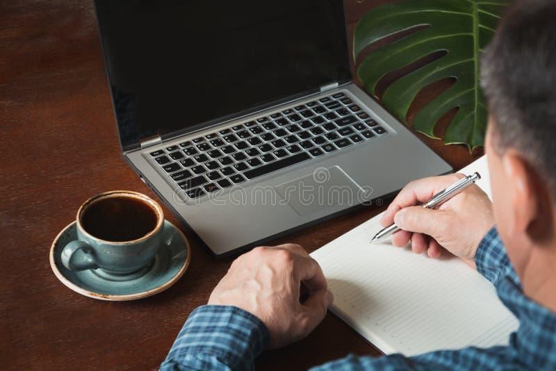 Achterdiemening van handen de bezige bedrijfsmens die door pen wordt geschoten en laptop met behulp van bij bureau schrijven royalty-vrije stock fotografie