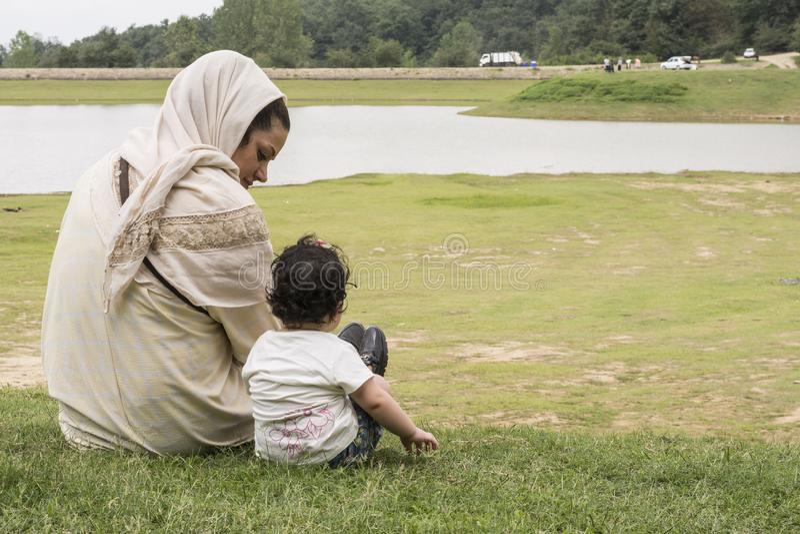 Achtereind van jonge moeder en haar weinig kind op openluchtgebied stock afbeeldingen