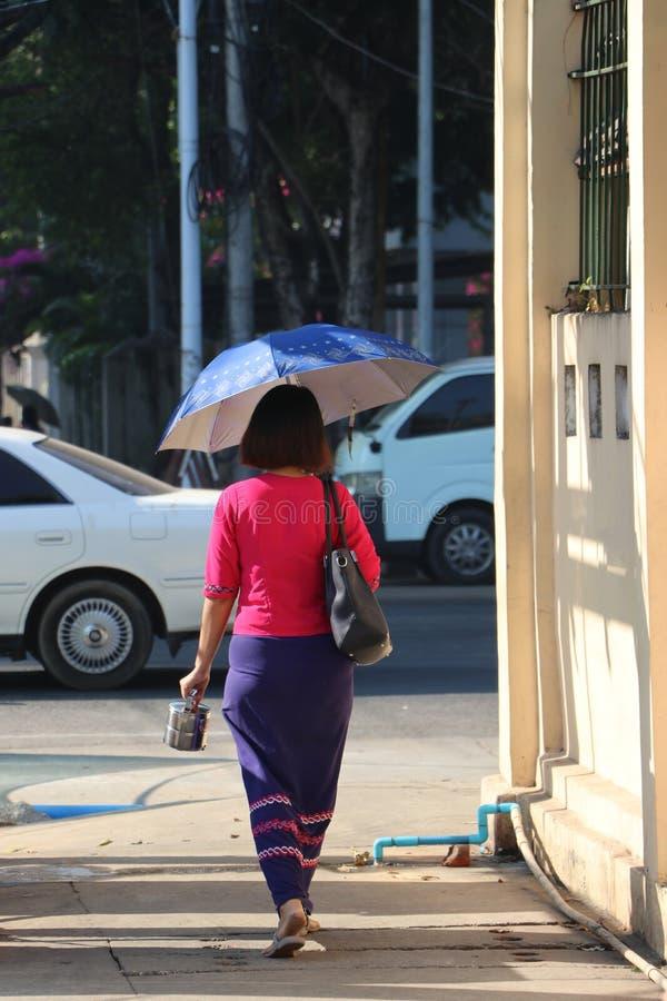 Achtereind van Myanmese-vrouw het lopen op de gang naast de straat stock afbeeldingen
