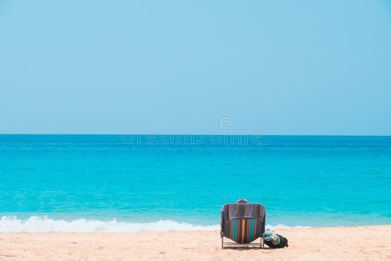 Achtergedeelte van de mens in hoed het ontspannen op ligstoel bij strand met overzees en blauwe hemelachtergrond royalty-vrije stock foto