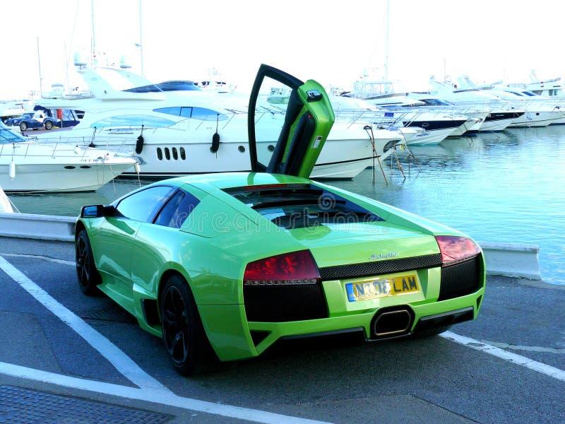 Achtergevelmening van een groene die Lamborghini-coupé bij kustlijn naast jachten wordt geparkeerd stock afbeeldingen