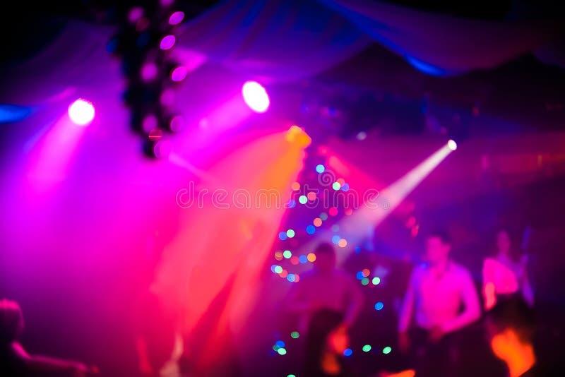 Achtergrond in de atmosfeer van de nachtclub met mensen en lasers bij partij stock afbeelding