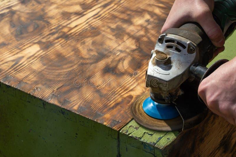 Achtergrond die houten oppervlaktemolen met schurend wiel malen de arbeiderstimmerman maalt het hout verwijderend de oude bril va royalty-vrije stock foto