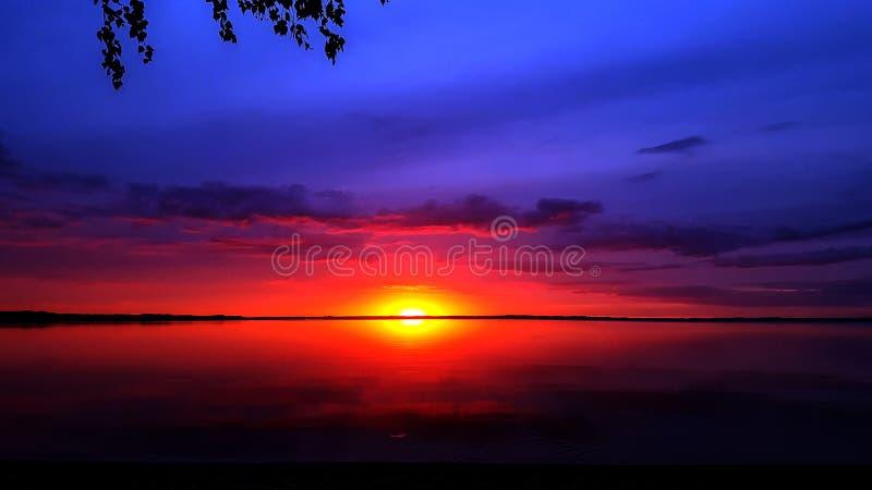 Achtergrond die met abstracte kleurrijke violette roze zonsondergangzon en bewolkte hemel in Razna-meerwater nadenken, Letland royalty-vrije stock fotografie