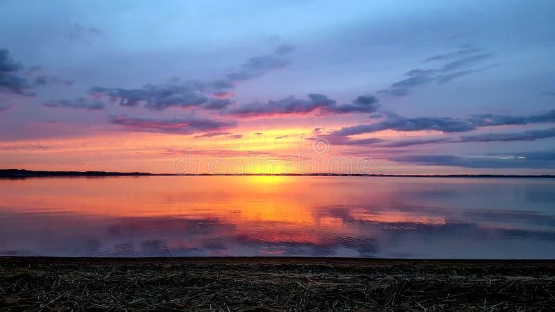 Achtergrond die met abstracte ultra purpere roze zonsondergangzon en bewolkte hemel in Razna-meerwater nadenken, Letland royalty-vrije stock fotografie