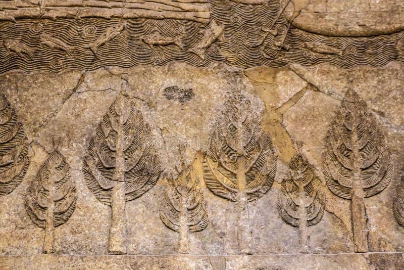 Achtergrond - het oude gebarsten en herstelde bas hulp snijden van oud Egypte van bomen en een stroom met vissen stock afbeeldingen