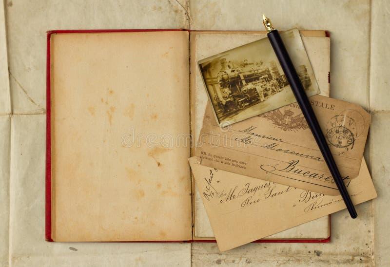 Achtergrond met uitstekende foto, prentbriefkaaren, en leeg open boek stock foto