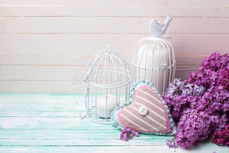 Achtergrond met verse lilac bloemen, kaarsen in decoratieve vogel stock fotografie