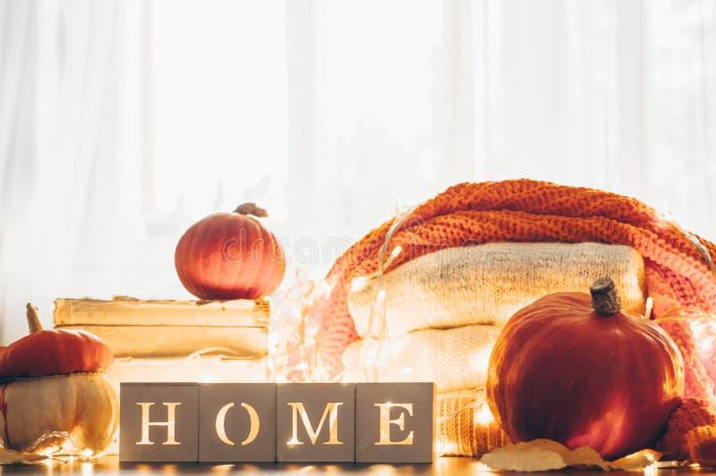 Achtergrond met warme sweaters en het inschrijvingshuis Stapel van gebreide kleren met bladeren, pompoenen coziness Het concept v royalty-vrije stock foto's