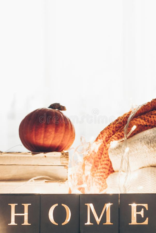 Achtergrond met warme sweaters en het inschrijvingshuis Stapel van gebreide kleren met bladeren, pompoenen coziness Het concept v stock foto