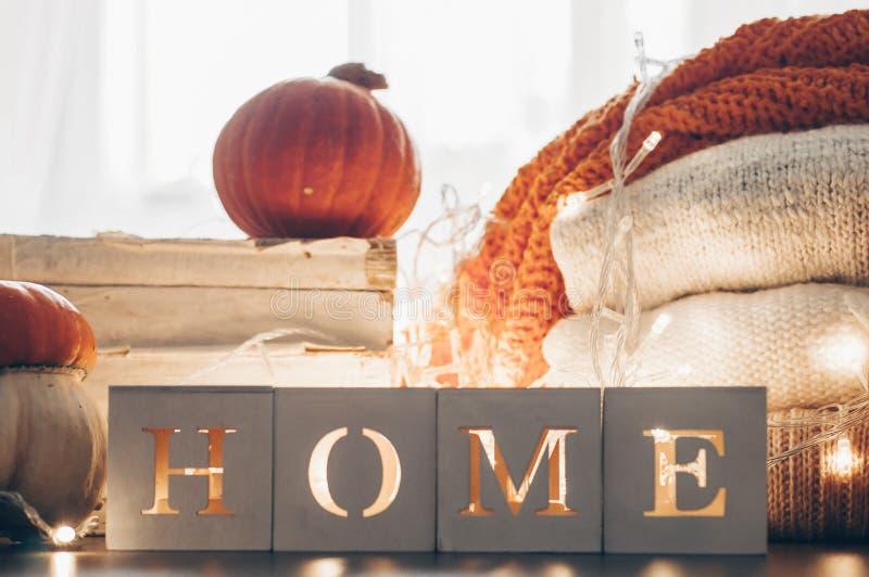 Achtergrond met warme sweaters en het inschrijvingshuis Stapel van gebreide kleren met bladeren, pompoenen coziness Het concept v stock foto's
