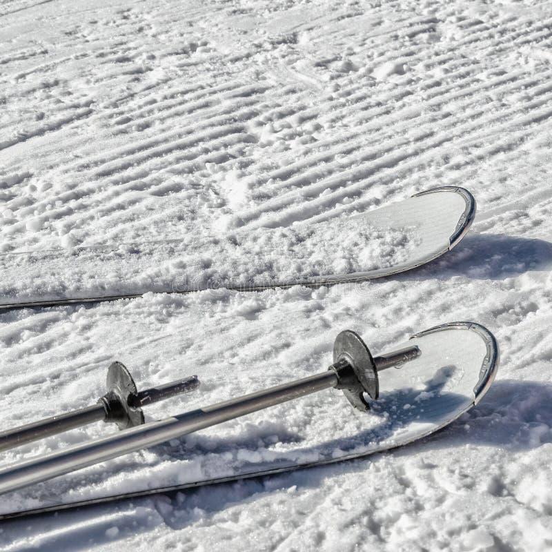 Achtergrond met witte skis en skistokken op sneeuw royalty-vrije stock afbeelding