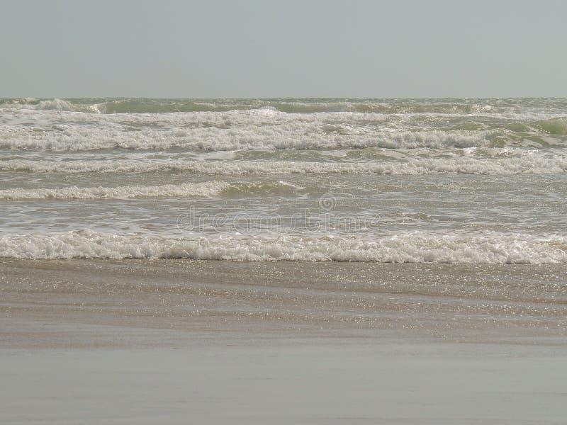 Achtergrond Overzeese golven met schuim het ranning op het zandige strand stock fotografie