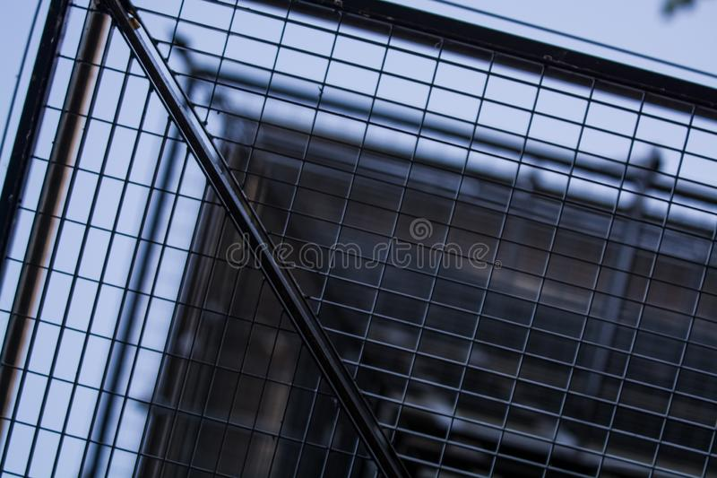 Achtergrond of textuur in de blauwe hemel van een dwarsligger van de bouw van roosters Weergeven van balkons van onderaan Kooi, n royalty-vrije stock afbeeldingen