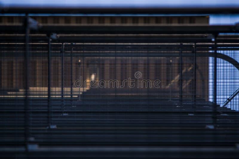 Achtergrond of textuur in de blauwe hemel van een dwarsligger van de bouw van roosters Weergeven van balkons van onderaan Kooi, n stock afbeelding