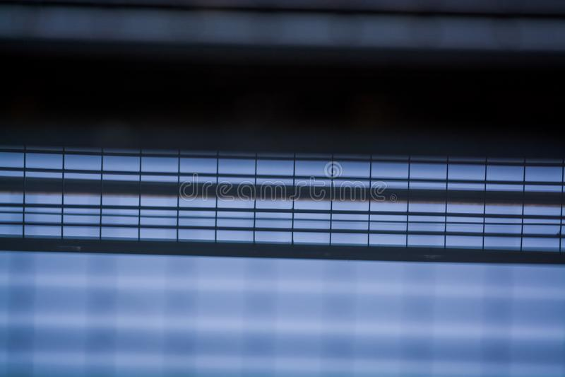 Achtergrond of textuur in de blauwe hemel van een dwarsligger van de bouw van roosters Weergeven van balkons van onderaan Kooi, n stock fotografie