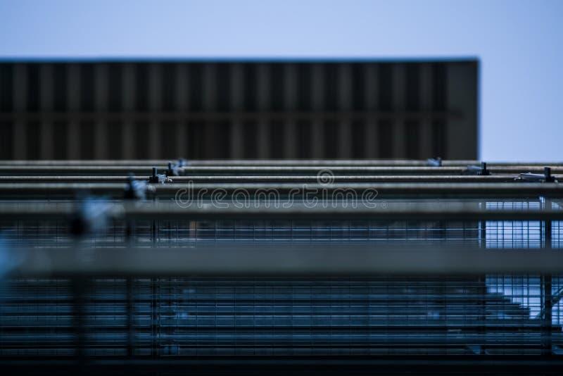 Achtergrond of textuur in de blauwe hemel van een dwarsligger van de bouw van roosters Weergeven van balkons van onderaan Kooi, n stock afbeeldingen