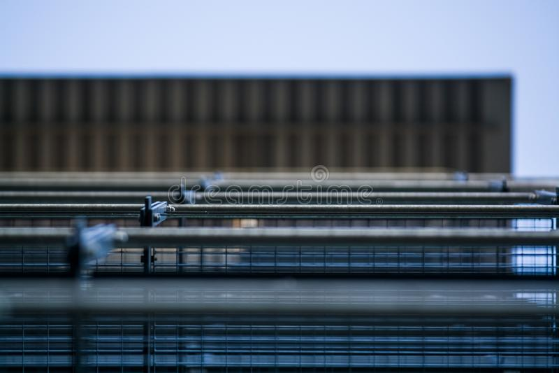 Achtergrond of textuur in de blauwe hemel van een dwarsligger van de bouw van roosters Weergeven van balkons van onderaan Kooi, n stock foto