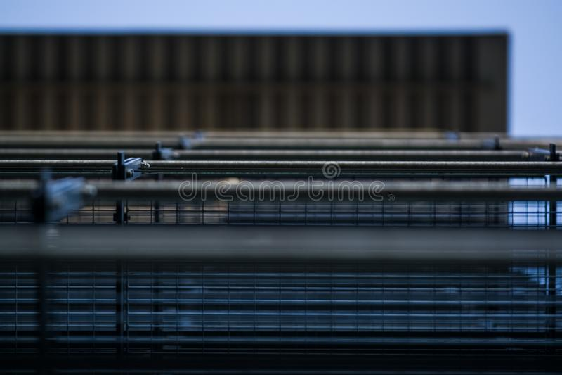 Achtergrond of textuur in de blauwe hemel van een dwarsligger van de bouw van roosters Weergeven van balkons van onderaan Kooi, n royalty-vrije stock fotografie