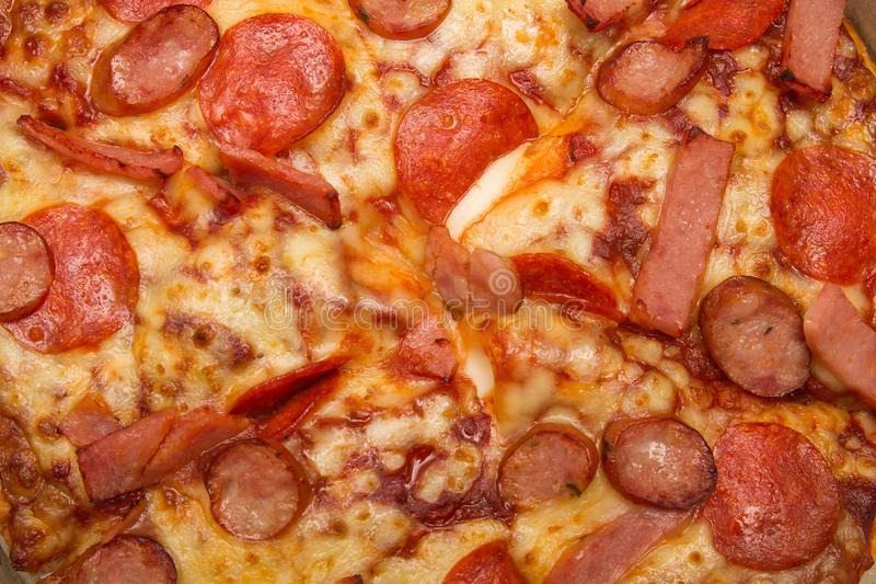 Achtergrond van close-uppizza met bovenste laagje van hammen, worsten en kaas stock foto