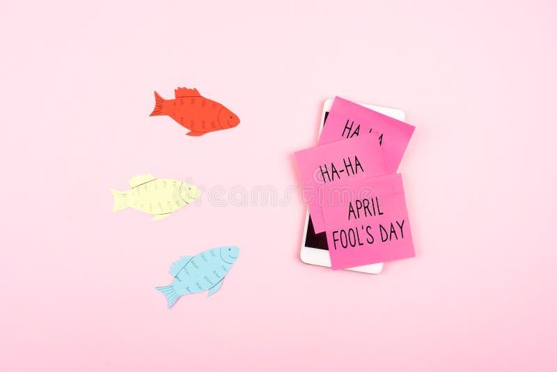 Achtergrond van de de Dagviering van April Fools de 'met document vissen, Smartphone en kleverige nota over roze achtergrond Alle stock afbeeldingen