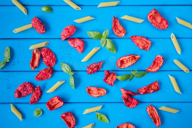 Achtergrond van in de zon gedroogde tomatenplakken met basilicumbladeren en penne deegwaren op blauwe houten lijst stock foto