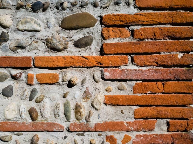 Achtergrond van een muur van baksteen en steen met concret wordt gecementeerd die stock foto