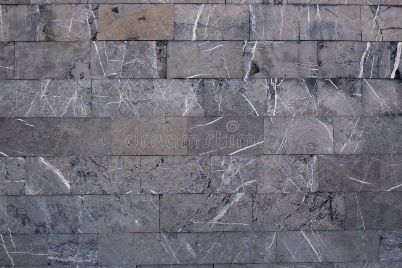 Achtergrond van grijze marmeren blokken Een muur van ruwe steen met zwarte potholes en witte lijnen stock afbeeldingen