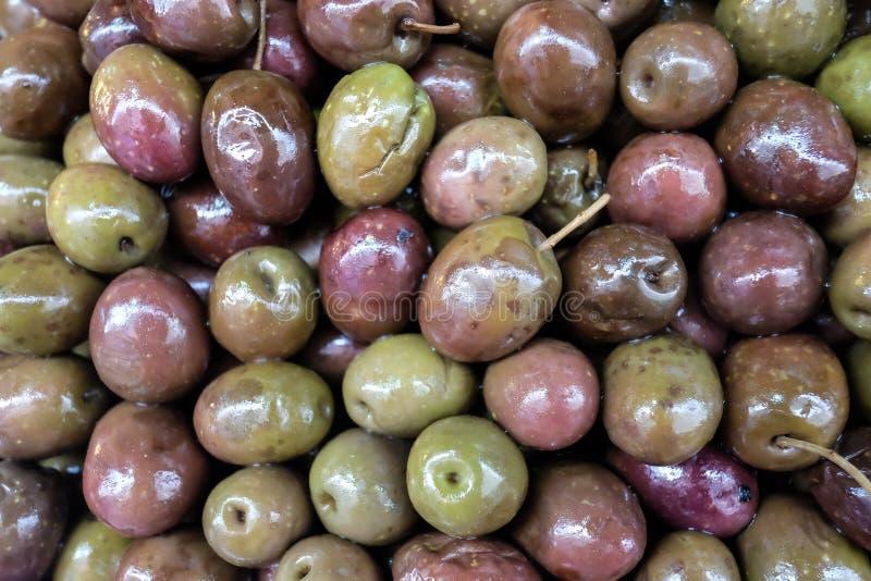 Achtergrond van ingelegde groene en roze olijven close-up stock fotografie