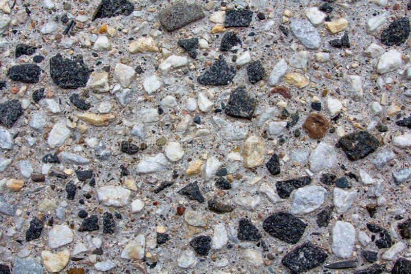 Achtergrond van kleine kiezelstenen in een concrete muur stock afbeelding