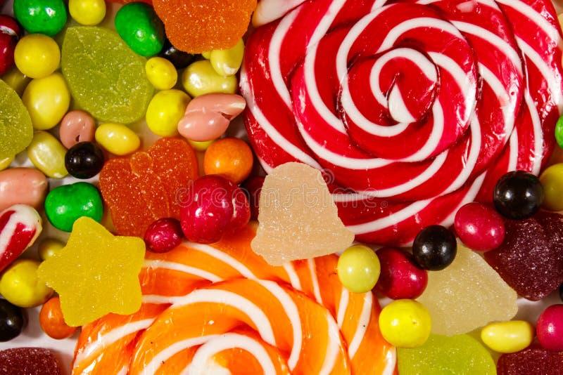 Achtergrond van kleurrijk chocoladesuikergoed, lollys, suikergoedriet en geleisnoepjes royalty-vrije stock fotografie