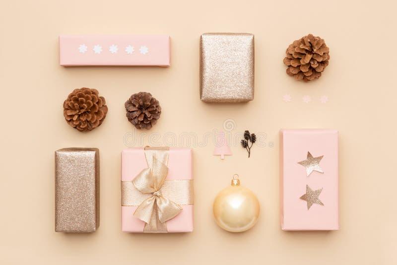 Achtergrond van pastelkleur de roze en gouden minimale Kerstmis Mooie noordse die Kerstmisgiften op beige achtergrond worden geïs stock afbeeldingen