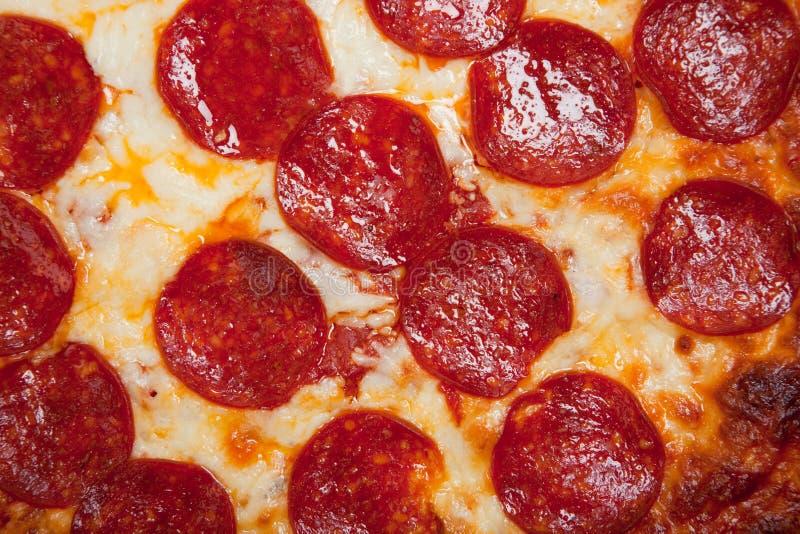 Achtergrond van pepperonispizza met kaas stock foto's