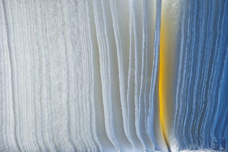 Achtergrond van poreus die document, met blauwe en gele LEIDENE lampen wordt verlicht Textuur en abstractie stock fotografie