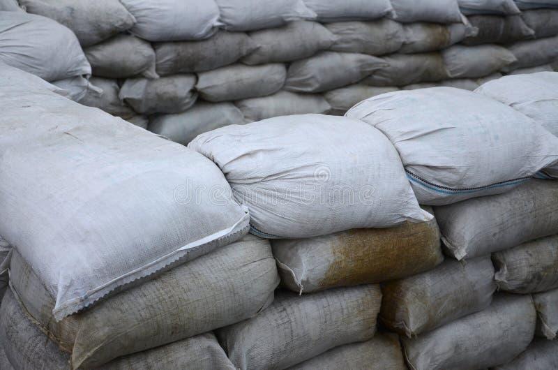 Achtergrond van vele vuile zandzakken voor vloeddefensie Beschermende zandzakbarricade voor militair gebruik Knappe tactische bun stock foto