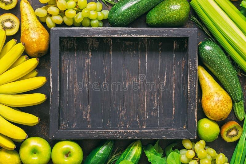 Achtergrond van verse groenten en vruchten met een leeg houten dienblad Kader van gele en groene groenten Een hoogste mening, een royalty-vrije stock afbeeldingen