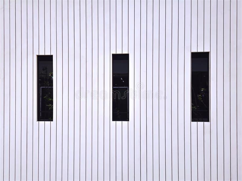Achtergrond van Witte Houten Plankmuur met Zwarte Lange Rechthoekige Vensters stock afbeelding