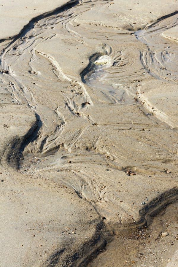 Achtergrond van zandige structuren in nat zand op het strand in golfpatronen royalty-vrije stock afbeeldingen