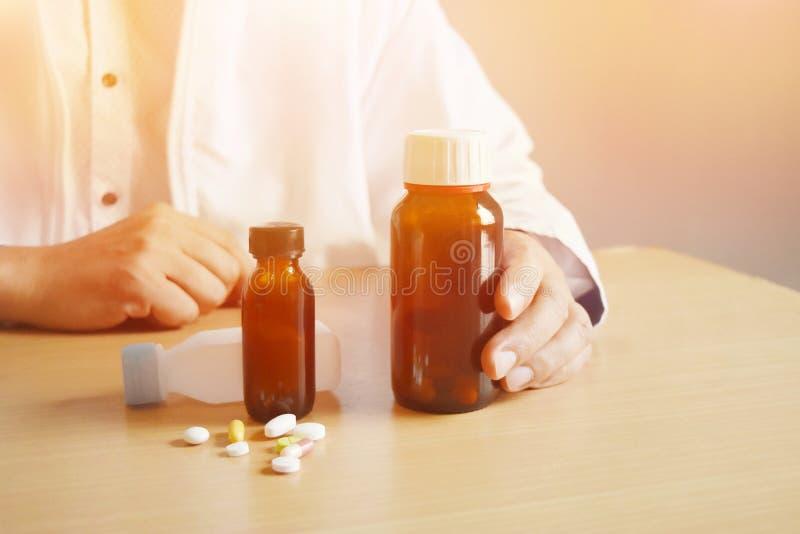 Achtergrond in warme lichte, Aziatische mens arts die een fles pillen op een bruine lijst en lege ruimte voor tekst houden royalty-vrije stock foto