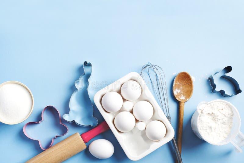 Achtergrondkader voor bakken Voorbereiding voor het bakken tijdens paastijd Ingrediënten en keukenartikelen voor het bakken stock foto's