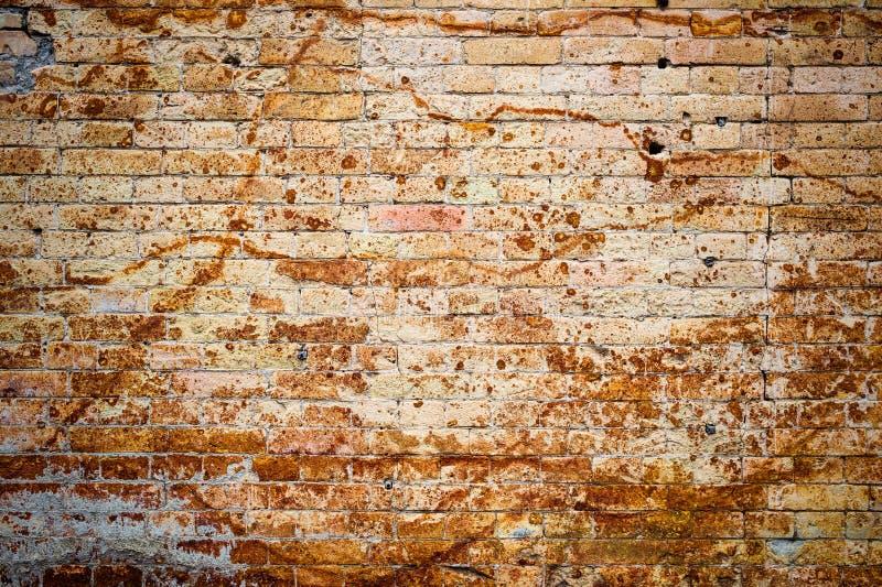 Achtergrondmuur van een oude gele uitstekende baksteen met roestige corrosiepatronen op de oppervlakte Geweven Achtergrond stock foto