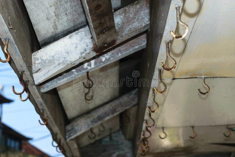 Achtergrondoppervlakte van oude en roestige haken die op het dak van winkel hangen stock foto's
