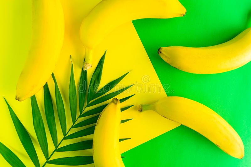 achtergrondpatroon van vers geel bananen en palmblad op een heldere gele en groene achtergrond Hoogste mening stock afbeeldingen