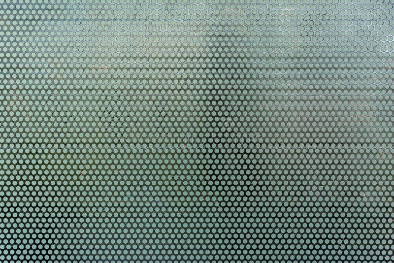 Achtergrondplaat van zwart metaalstaal van ronde gaten Naadloos oppervlak en structuur van roestvrij stalen patroon stock foto