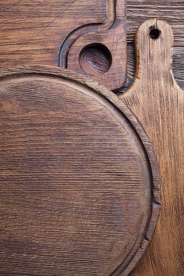 Achtergrondsjabloon van hout - klassieke snijplaten op bruine houten tafel stock afbeeldingen