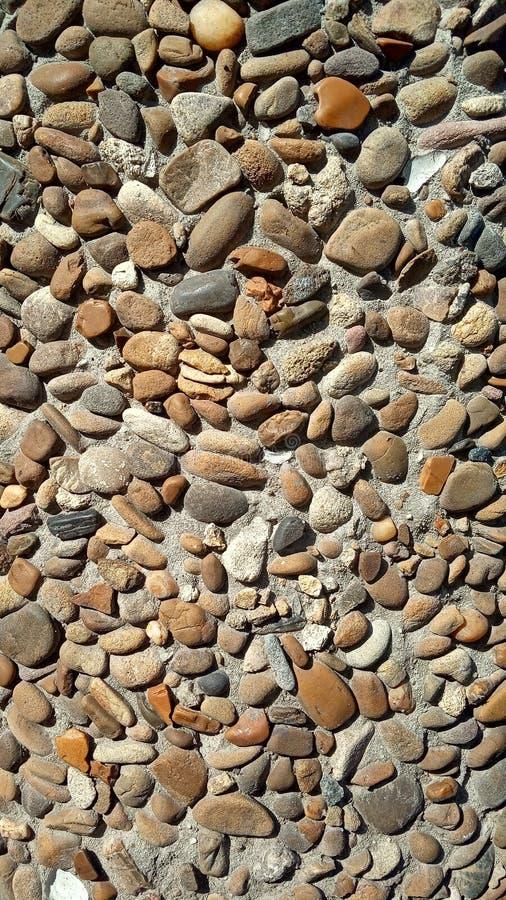Achtergrondtextuur bruine kiezelstenen in een concrete muur stock fotografie