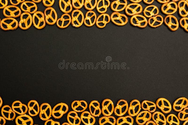 Achtergrondtextuur van gezouten smakelijke minipretzels in de traditionele vorm van de scharnierassemblage over een zwarte achter stock afbeelding