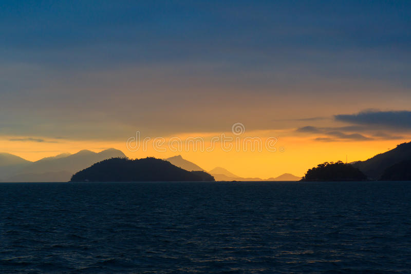 Achtergrondzonsondergang overzees bergeneiland Ilha Grande, Brazilië royalty-vrije stock foto