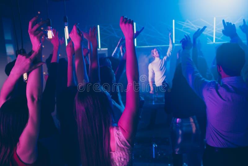 Achterkant foto van gekke fellows dansende vloerbeweging zet handen omhoog met het gevoel van vreugde disco discotheque stock afbeelding